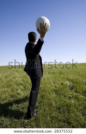 businessman in the field trowing a soccer ball - stock photo