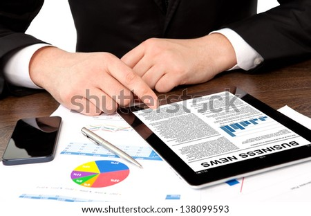 businessman in the office at the table watching business news on tablet computer screen - stock photo