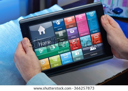 businessman in the office holding a tablet and looking screen interface application /man working with the software of tablet pc at home - stock photo