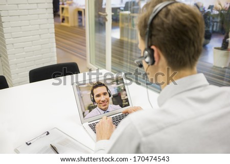 Businessman in the office on videoconference with headset, Skype - stock photo