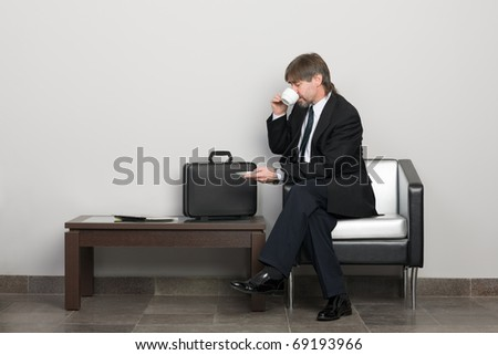 Businessman in the waiting room drinking coffee. - stock photo