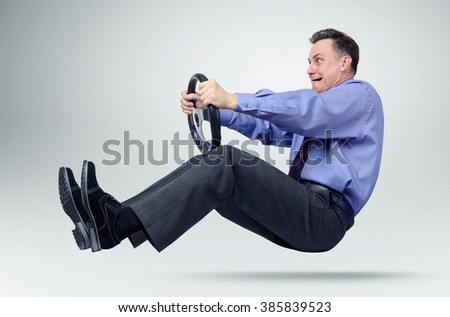 Businessman in tie car driver with a steering wheel - stock photo