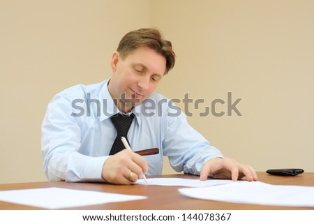 Businessman in tie sits at table and signs documents in office. - stock photo