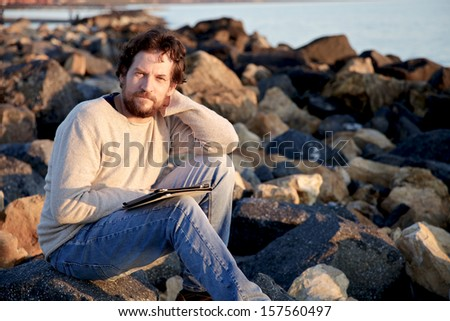 Businessman in vacation working with tablet - stock photo