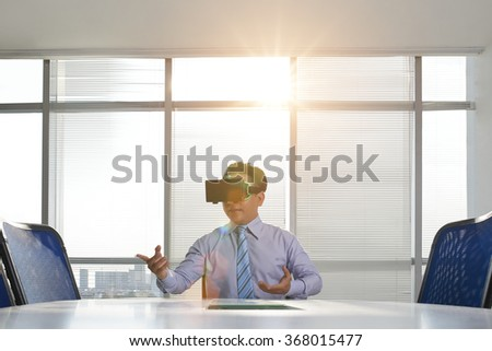 Businessman in virtual reality goggles holding business meeting in the office - stock photo