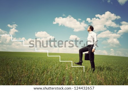 businessman in white shirt walks up the ladder in the green field - stock photo