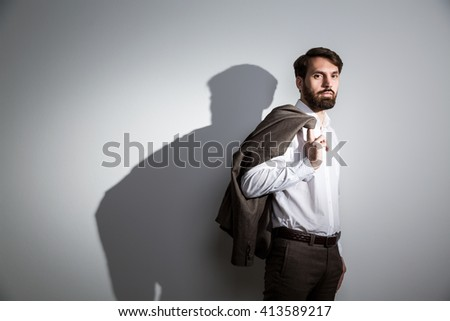 Businessman in white shirt with suit jacket on shoulder standing against wall with shadow - stock photo