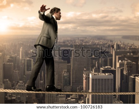 Businessman is balancing on a rope - stock photo