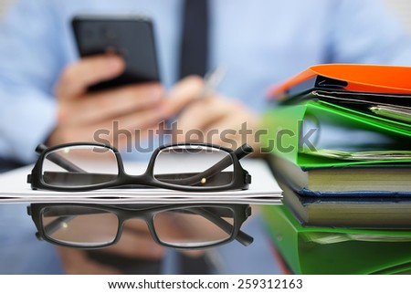 businessman is calling financial adviser for help.Focus on glasses - stock photo