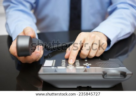 businessman is dialing on telephone keypad - stock photo