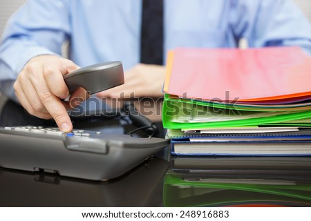Businessman is dialing  phone for advice when he got a lot of files. Assistance is needed - stock photo