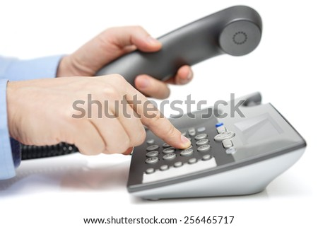 Businessman is dialing telephone number with handset in hand - stock photo
