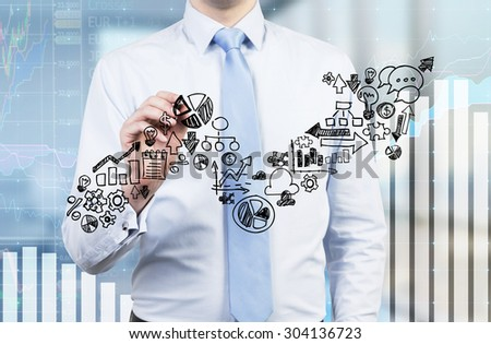 Businessman is drawing a growing arrow on the glass screen. Business icons as an integral part of the growing graph. Charts on the background. - stock photo