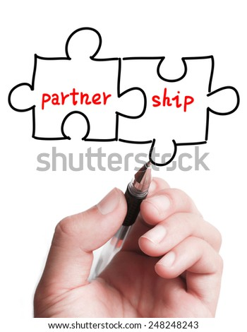 Businessman is drawing a Partnership puzzle concept on the transparent virtual screen. - stock photo