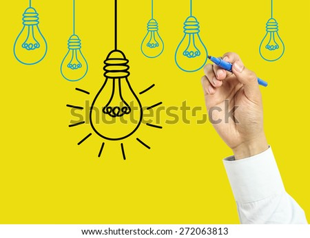 Businessman is drawing bulbs with marker on transparent board with yellow background. - stock photo
