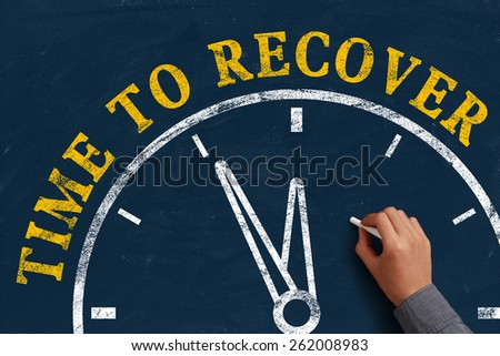 Businessman is drawing the concept of time to recover on chalkboard. - stock photo