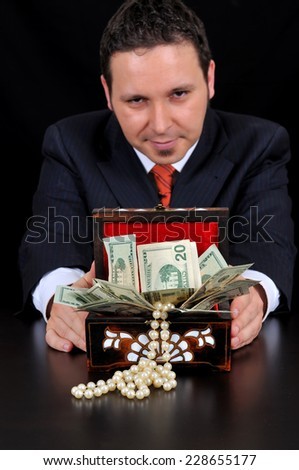 Businessman is extending gift box. Maybe bribing on the black background - stock photo