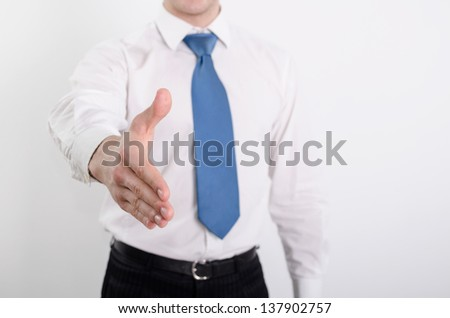 Businessman is going to shake your hand. Shallow depth of field, focus on finger-tips. - stock photo