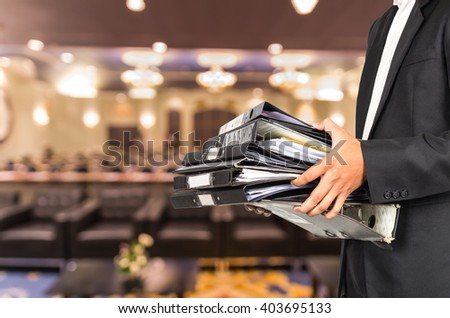 Businessman is holding many document folders on Abstract blurred photo of conference hall or seminar room background, business busy concept - stock photo