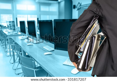 Businessman is holding many document folders on Abstract blurred photo of empty server room, back side, business busy concept - stock photo