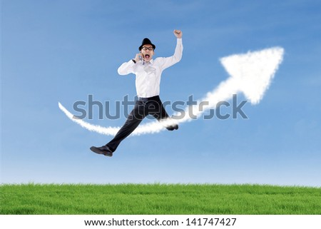 Businessman is jumping and calling with his phone over up arrow sign cloud - stock photo