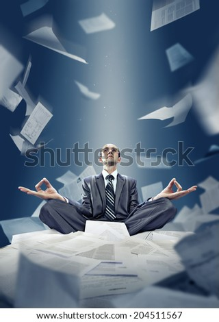 Businessman is meditating with documents - stock photo