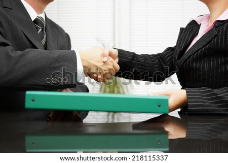 businessman is passing binder with documentation  to his client while handshaking - stock photo
