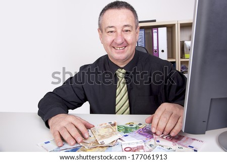 Businessman is pleased with his money on the desk - stock photo