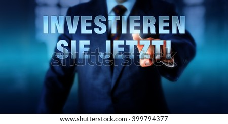 Businessman is pressing INVESTIEREN SIE JETZT! on a touch display interface. German language call to action meaning DO INVEST NOW. Virtual text on a transparent visual screen. Financial concept. - stock photo