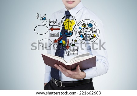 Businessman is reading a book with flying business management flowchart. - stock photo