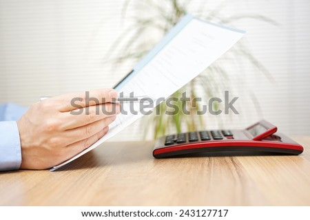 businessman is reading and checking contract - stock photo