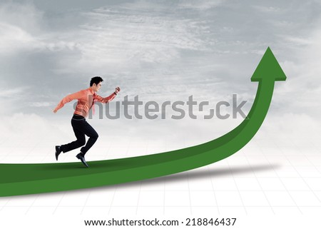 Businessman is running on line chart to achieve profit - stock photo