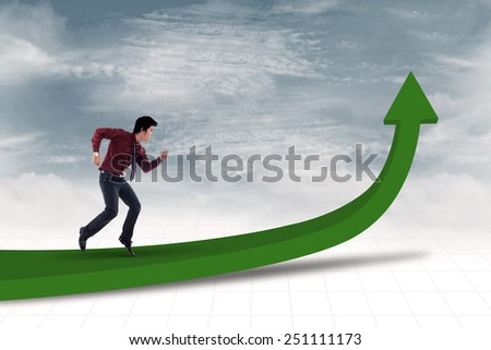 Businessman is running toward the goal to achieve profit under blue sky - stock photo