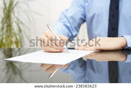 businessman is signing contract to finalize deal - stock photo