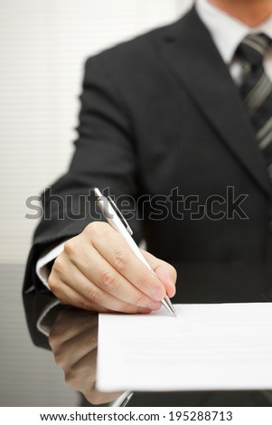 businessman is signing document - stock photo