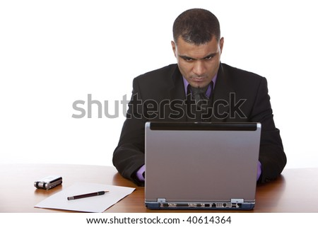 Businessman is sitting on his desk and working on his laptop. Isolated on white. - stock photo