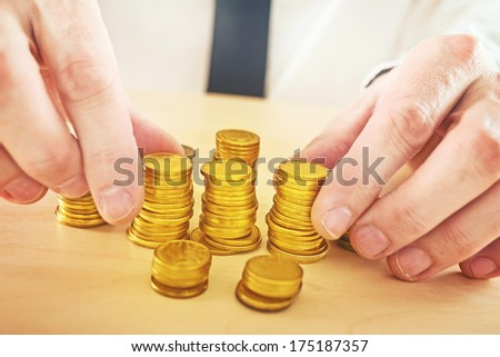 Businessman is stacking golden coins. Business profit and money savings concept. - stock photo