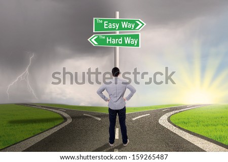 Businessman is standing on the road with sign of easy vs hard way - stock photo