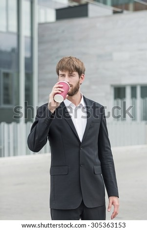 Businessman is standing outside company drinking coffee - stock photo