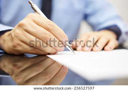 businessman is writing a letter or signing a agreement - stock photo