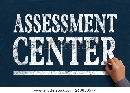 Businessman is writing Assessment center text on blue chalkboard. - stock photo