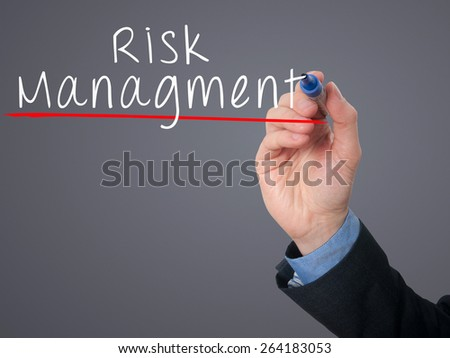 Businessman is writing Risk Management on the transparent board. Isolated on grey background. Stock Image - stock photo