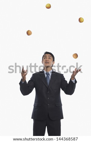 Businessman juggling with apples - stock photo