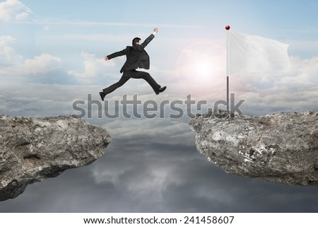 Businessman jump on cliff with blank white flag and natural sunlight cloudscapes background - stock photo