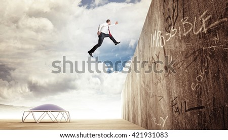 businessman jump over concrete wall - stock photo