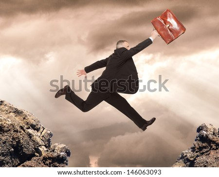 Businessman jumping between two rocks - stock photo