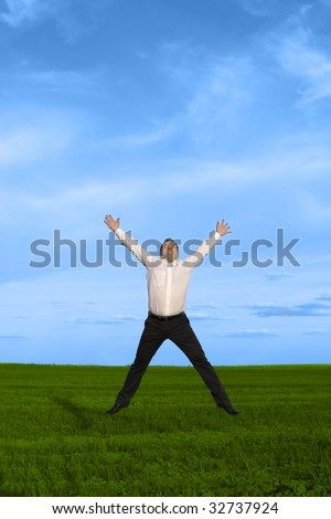 Businessman jumping on the green grass over clouds blue sky - stock photo