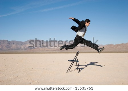 Businessman jumping over a chair - stock photo