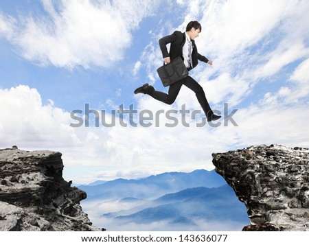 businessman jumping over danger precipice on the mountain, concept for business, asian people - stock photo