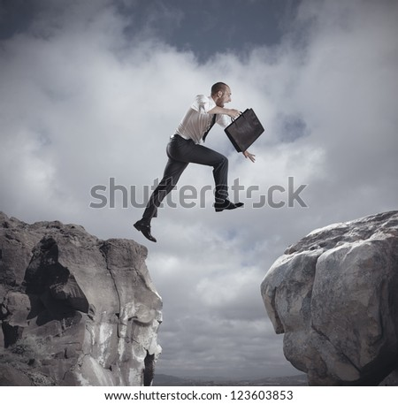 Businessman jumping over the mountains. concept of ambition in business - stock photo